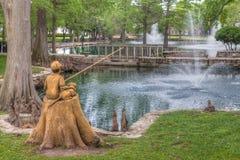 Jungen-und Hundefischen-Skulptur in Theta-Teich Stockfotos