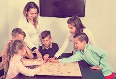 Jungen und kleine Mädchen, die am Brettspiel spielen stockbild