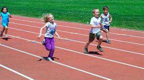 Jungen und Mädchen auf dem Spaßlack-läufer Stockfotos
