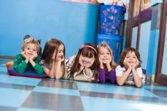Jungen und Mädchen, die auf Boden im Kindergarten liegen lizenzfreie stockbilder