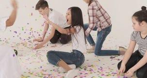Jungen und M?dchen, die den Spa? spielt mit Konfettis auf Boden haben stock video