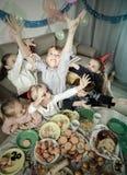 Jungen und Mädchen, die sich im Scherz während des friend's Geburtstagsteils benehmen lizenzfreies stockfoto