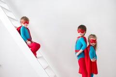 Jungen und Mädchen, die Superhelden spielen stockbild
