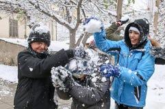 Jungen und Mädchen spielen mit Schneebällen in Saloniki Lizenzfreie Stockfotos