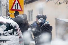 Jungen und Mädchen spielen mit Schneebällen in Saloniki Stockfotografie