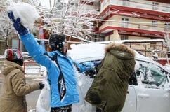 Jungen und Mädchen spielen mit Schneebällen in Saloniki Lizenzfreies Stockfoto
