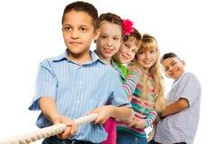 Jungen und Mädchen ziehen das Seil stockbild