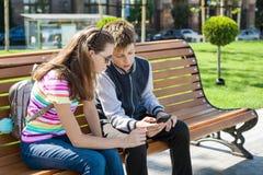 Jungen- und Mädchenjugendliche spielen, gelesen, Blick am Smartphone Auf der Bank der städtische Hintergrund stockfoto