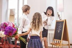 Jungen- und Mädchenkinder geben Blumen als Schullehrer im teache Stockfotografie