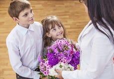 Jungen- und Mädchenkinder geben Blumen als Schullehrer im teache Lizenzfreies Stockfoto