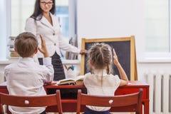 Jungen- und Mädchenkinder mit dem Lehrer in der Schule hat ein glückliches Lizenzfreie Stockfotos