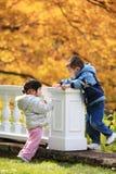 Jungen- und Mädchenkleinkinder, die in den Herbstblättern spielen Stockbild