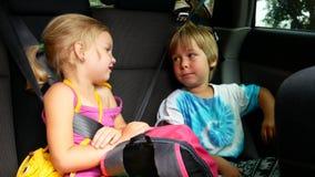 Jungen- und Mädchenreiten im Auto stock video