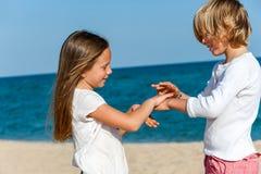 Jungen- und Mädchenspielhandspiel auf Strand. Stockfoto