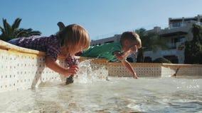 Jungen- und Mädchenspritzen im Brunnen Junge Erwachsene stock video footage