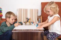 Jungen- und Mädchenzeichnung auf Papier Stockfoto