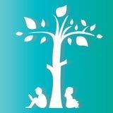 Jungen- und Mädchenlesung unter einem Baum Stockfotos