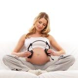 Jungen und schwangeren blonden Holdingkopfhörer Lizenzfreie Stockfotos