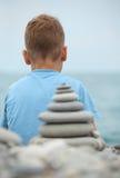 Jungen- und Steinstapel, hintere Ansicht Stockfotografie