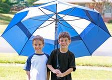 Jungen unter einem Regenschirm Lizenzfreie Stockfotografie