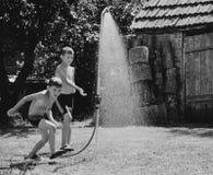 Jungen unter einer Dusche im Garten lizenzfreie stockfotografie