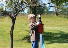 Jungen-waschender Golfball stockbild