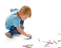 Jungen-Zeichnung mit Kreide Stockfotos