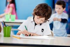 Jungen-Zeichnung mit Skizze Pen At Desk In Lizenzfreie Stockfotos