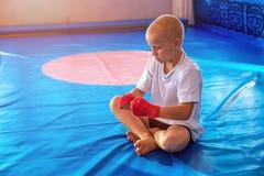 Jungenboxer in der Turnhalle wickelt seine Hände mit Verbänden ein stockbild