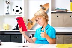 Jungendaumen, der ein Buch hoch und gelesen worden sein würden Lizenzfreie Stockfotografie