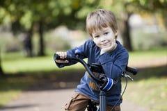 Jungenfahrt ein Fahrrad im Stadtpark Lizenzfreies Stockfoto