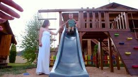 Jungenfahrt zum Kind-` s schiebt, das Kind, das mit Eltern, eine Mutterunterstützung sein Sohn, die glückliche Familie spielt, di stock video
