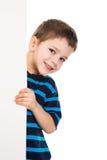 Jungenflüchtiger blick heraus von der vertikalen weißen Fahne Stockfotos