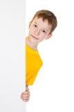 Jungenflüchtiger blick heraus von der vertikalen weißen Fahne Stockfotografie