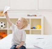 Jungenfliegendes Papierflugzeug im Schlafzimmer Stockfotografie