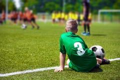 Jungenfußballspieler auf Sportfeld Kind, das auf Fußballrasenfläche sitzt Lizenzfreie Stockbilder
