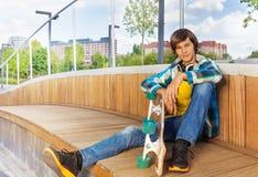 Jungengriffe fahren Skateboard während mit dem Arm auf Knie sitzt Stockfoto
