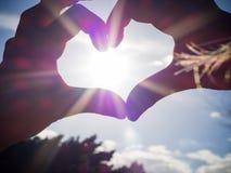 Jungenhände bilden ein Herz gegen die Sonnenstrahlen lizenzfreies stockbild