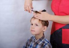 Jungenhaarschnitt mit Scheren Lizenzfreies Stockfoto