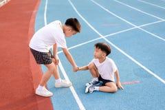 Jungenhelfer vom Fallen laufen gelassen Stockfoto