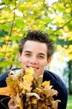 Jungenholding-Herbstblätter Stockbilder