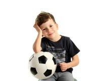 Jungenholdingfußballkugel und -erholung lizenzfreie stockfotografie