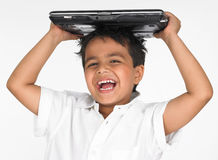 Jungenholdinglaptop auf seinem Kopf Lizenzfreie Stockbilder