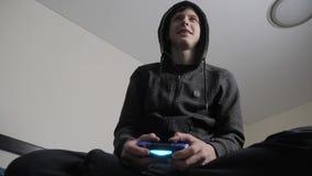 Jungenjugendlicher in der Haube, die Videospiele auf der Konsole auf dem gamepad spielt Mit Kapuze Strickjacke junges jugendlich  stock footage