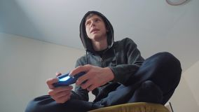 Jungenjugendlicher in der Haube, die Videospiele auf der Konsole auf dem gamepad spielt Mit Kapuze Strickjacke junges jugendlich  stock video footage