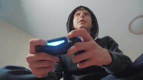 Jungenjugendlicher in der Haube, die Videospiele auf der Konsole auf dem gamepad spielt Mit Kapuze Strickjacke junges jugendlich  stock video