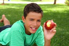 Jungenjugendlicher, der roten Apfel auf Gartengras isst Stockbilder