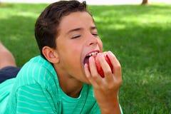 Jungenjugendlicher, der roten Apfel auf Gartengras isst Stockfotos