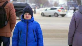 Jungenjugendlicher in einem Blau hinunter die Jacke, die auf der Straße steht Autos reiten in den Hintergrund, der Junge aufpasst stock footage