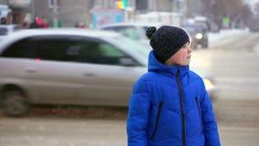 Jungenjugendlicher in einem Blau hinunter die Jacke, die auf der Straße steht Autos reiten in den Hintergrund, der Junge schaut h stock video